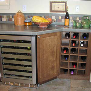 remodeled kitchen with focus on wine storage, counter, and tile backsplash